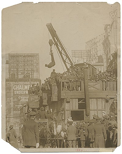 Houdini, Harry (Ehrich Weiss). Houdini Straitjacket Challenge Escape Photo. New York: Underwood & Underwood, ca. 1920. A large crowd attends the challenge, Houdini shown dangling upside-down from a construction crane. Stamped on verso by the