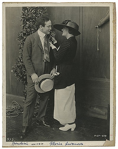 Houdini, Harry (Ehrich Weiss). Publicity Photograph of Houdini with Gloria Swanson. Lasky Studios, (1919). Silver gelatin print depicting Swanson tying a rose to HoudiniÍs lapel. 10 x 8î. Mounted on board, chipped in lower right slightly affecting