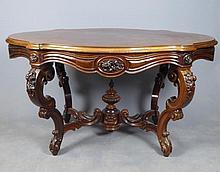 TABLE DE MILIEU en palissandre ouvrant à deux tiroirs en ceinture, le plateau chantourné, les pieds en double console richement sculpté, réunis par une entretoise en X. Fin du XIXème siècle. 71 x 126 x83 cm (petites rayures)