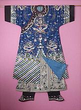 CHINE : Robe dragon en kesi à décor de dragons pourchassant la perle sacrée parmi les nuages et emblèmes bouddhiques au dessus des vagues écumantes sur fond bleu. H (robe): 166 cm. Petites usures et retouches. Encadrement bois et