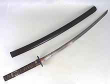 SABRE JAPONAIS dit Katana à poignée en bois recouverte de galuchat et d'un tressage, tsuba en fer ajouré, lame acier, avec fourreau.  Longueur totale: 93 cm. Usures et accidents.