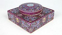 CHINE: Bonbonnière de forme carrée en porcelaine à décor en émaux polychrome de fleurs de lotus, et feuillages. Au revers de la base, la marque Qianlong. H: 5.5 - L: l: 11.5 cm