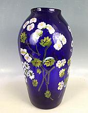 MURANO : Important vase en verre soufflé bleu à motif de marguerites, roses, pensées et feuillage incrustés dans la masse (murrines ?). Vers 1900. Col très légèrement rodé. H : 43cm environ.