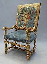 FAUTEUIL à haut dossier en bois mouluré et doré, les accotoirs à enroulements feuillagés, pieds tournés réunis par une entretoise en H. Style Louis XIV composé d'éléments anciens. Garniture en tapisserie au point à décor floral. 120 x 60