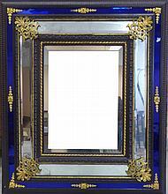 MIROIR rectangulaire à parecloses en bois noirci et verre blanc et bleu orné dans les écoinçons de rinceaux et palmettes en bronze doré. Fin du XIXème siècle. 126 x 106 cm. Usures à la glace.