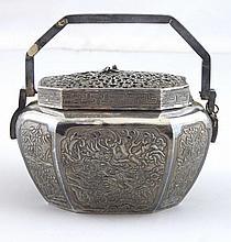 INDOCHINE: Brûle-parfum à anse en argent et métal à riche décor de phoenix parmi des paysages, le couvercle ajouré.  Marque incisée au revers de la base. XIXème siècle; H : 9 - L: 12cm. Usures, une anse manquante.