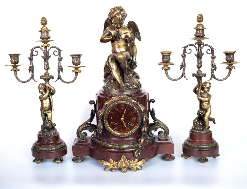 Set of a clock made in bronze on stone base with sculpture after Clodion of a sitting Putti and 2 bronze candlesticks with stone base and sculptures with standind Putti inspired by Clodion on each candlestick.