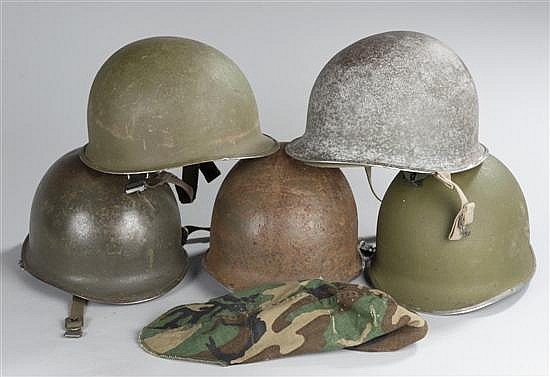 Collection of 5 US GI helmets, 2 from WWII, 3 post war, and 1 current helmet cover. In good to very good condition.