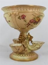 A ROYAL WORCESTER TABLE CENTREPIECE, painted with flowers on blush ivory ground. The base with three cornucopia shaped vases and lio...
