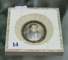 A MINIATURE PORTRAIT IN IVORY FRAME, depicting the portrait of a gentleman wearing a blue and red coat. Height 10.5cm.