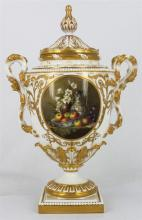 A ROYAL WORCESTER COVERED URN, double naturalistic handle, of ovoid form, on an acanthus capped base, the centre painted with a stil...