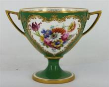 A ROYAL WORCESTER DOUBLE HANDLED CUP, painted with a bouquet of flower on a green ground, heightened in gilt, signed Ernest Phillips...