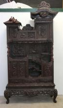 A JAPANESE CARVED HARDWOOD CABINET, Meiji period (late 19th century), the cabinet carved in red wood on scroll feet, comprising two...