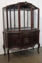 A LOUIS XV STYLE DISPLAY CASE, the one door glass cabinet ornamented with brass decoration, the bow front base opening on three set...