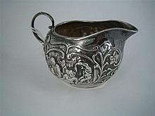 A DUTCH SILVER CREAM JUG relief decorated with domestic idylls within foliate borders.