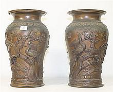A PAIR OF CHINESE BRONZE VASES, with high relief design of Phoenix in a tree. ht. 30cm.