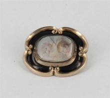 AN ANTIQUE GOLD AND ENAMEL BROOCH, oval scrolled design, black enamel inlay, picture panel; testing as 9ct gold. Weight 10.2g.