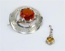 A STERLING SILVER BROOCH, round with orange glass inset, William Henry Leather, Birmingham 1908. Diameter 4.5cm. Together with a yel...