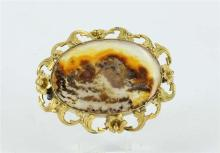 AN ANTIQUE-STYLE MOSS AGATE BROOCH, floral and scrolled detail; gold plated.
