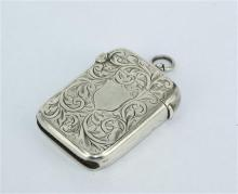 A STERLING SILVER VESTA CASE, shield and foliate design, William Hair Haseler, Birmingham, 1911. Length 4.7cm. Weight 21.7g.