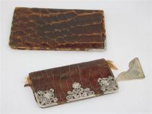 TWO CROCODILE SKIN WALLETS, one with a silver corner, L.Spiers, Birmingham, 1924 (16.5 x 11cm), one mounted with Art Nouveau silver...