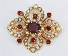 AN EDWARDIAN STYLE BROOCH, oval and round cut garnets with split pearls, all set in 9 carat yellow gold, London 1970. Length 4cm. We...