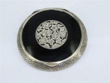 A STERLING SILVER COMPACT, onyx inset lid, mirror and gilded interior. Diameter 5.5cm. Stamped sterling.