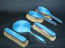 A FIVE-PIECE ENAMEL AND SILVER DRESSING TABLE SET, mirror, pair of hair brushes and pair of clothes brushes, pale blue transulcent e...