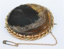 *AN AGATE BROOCH, agate section set in a heavy rope twist gold mount, safety chain attachment, back of agate section lacqured; 9ct g...
