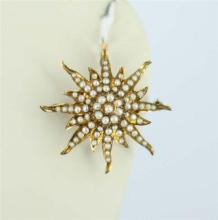 AN ANTIQUE GOLD AND SEED PEARL PENDANT / BROOCH, sunburst form, curved rays; 14ct gold. Weight 6.6g.