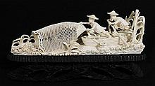 A CHINESE IVORY CARVING, two fishermen casting net, on wooden stand. lt 9.3cm.