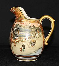 A JAPANESE SATSUMA CREAM JUG, finely painted with landscape and floral design. ht 10cm
