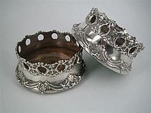 A PAIR OF SILVER-PLATE WINE COASTERS, each with applied openwork strapwork sides; oak bases.
