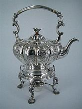 A SILVER-PLATE KETTLE, engraved and embossed with foliate ornament, on cast spirit burner stand with shell feet. Height 34.5cm.