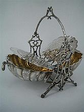 A SILVER-PLATE BISCUIT SACHET, shell form, engraved with flower and leaf and with rustic stand. Height 27cm.