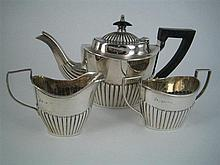 AN EDWARDIAN SILVER BACHELOR TEA-SET, three pieces, each half-fluted, the pot with ebony handle and finial; J.M.Banks, Chester 1901....