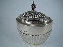 A SILVER TEA CADDY, oval, half-fluted; Isadore Leapman, Birmingham 1912. Height 11cm. Weight approx 350g.