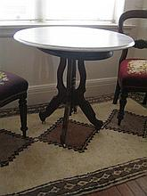 A CIRCULAR MARBLE-TOPPED LAMP TABLE with walnut base and ceramic castors. Diameter 77cm.