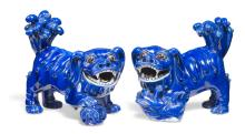 A pair of porcelain Fo-dogs in blue glaze, the he with a ball under the paw and the she with a puppy under the paw. 19th century.