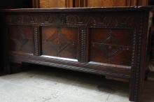 Coffre en bois naturel ciré, sculpté de losanges et de motifs de feuillages.