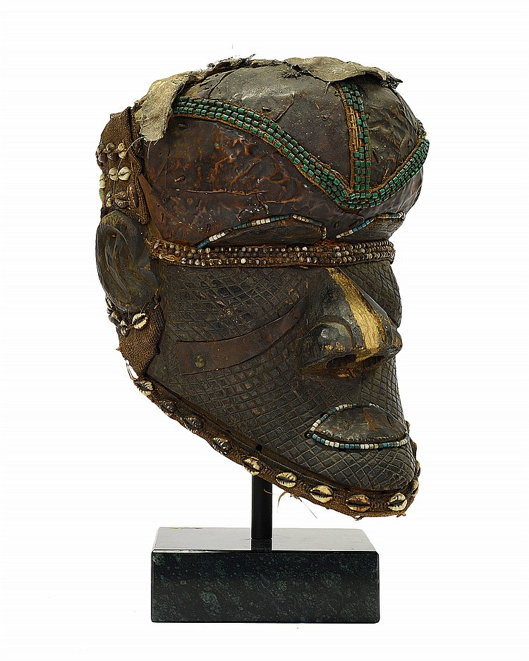 A WOODEN MALE IVORY COAST HELMET MASK WITH BRONZE, BEAD, SHELL, AND HIDE DECORATION,