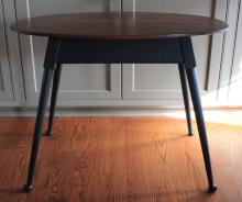 """Furniture: RC –  a very clean, likely David Smith Co. unmarked oval  natural finish cherry top lamp or side table on a painted black splayed  four-leg base with Queen Anne type feet, 35 ¼""""W X 22 ½""""D X 26 ½""""T  (VG)  PICK UP ONLY"""