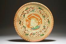 A Werra red earthenware pottery plate with a man's bust, dated 1611