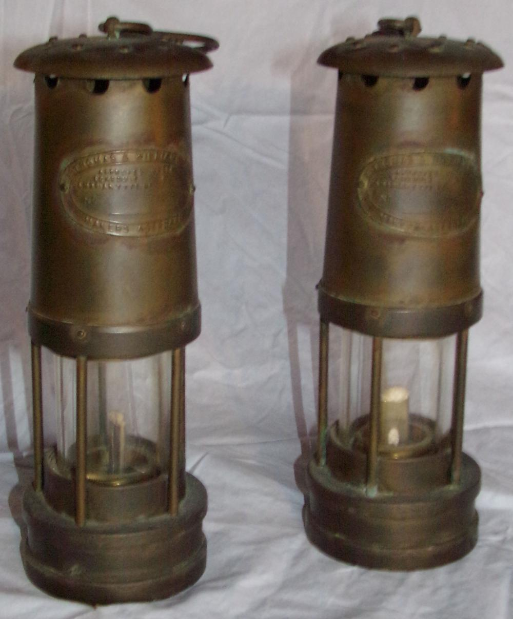 "Pair of brass lanterns marked E. Thomas & Williams, Ltd. Makers Aberdore, with hook hangers, each are 9 5/8"" T x 3 3/8"" base diameter"