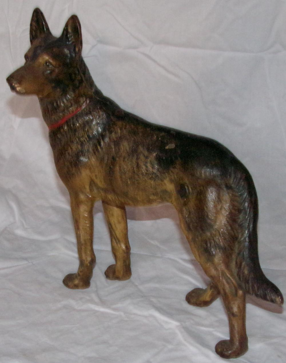 "Vintage cast iron German Shepherd dog form doorstop in standing position, painted with a red collar, some paint loss & rust visible, 9 3/8"" T x 10"" L x 2 ¾"" D"