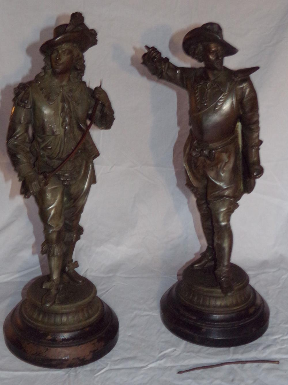 "Pair of vintage cast/ white metal statues, ""Three Musketeers"" type figures with swords, each mounted on round weighted iron bases, 1 sword needs to be reattached, piece is with figure, each 20 ¾"" x 20"" T, bases each 7 5/8"" D"