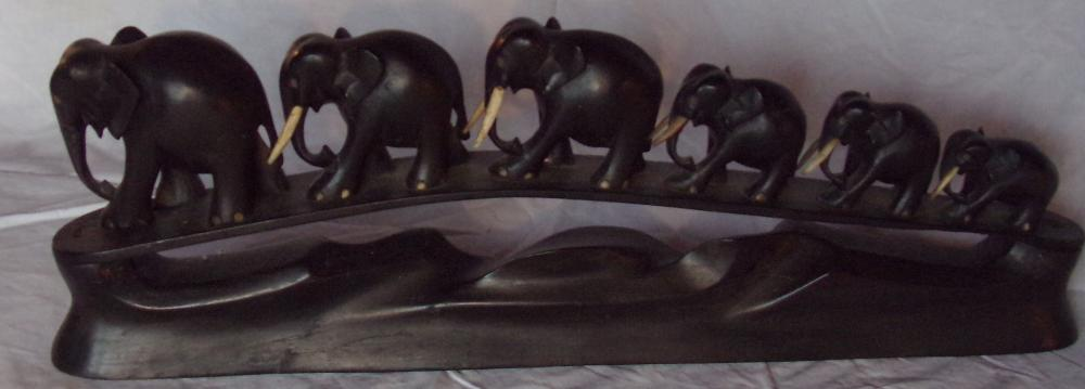 "Ebony wood carving of 6 elephants in graduated sizes walking, mounted on an oval carved base, front 2 elephants are missing tusks, 6"" T x 17 3/8"" L x 1 3/4"" D"