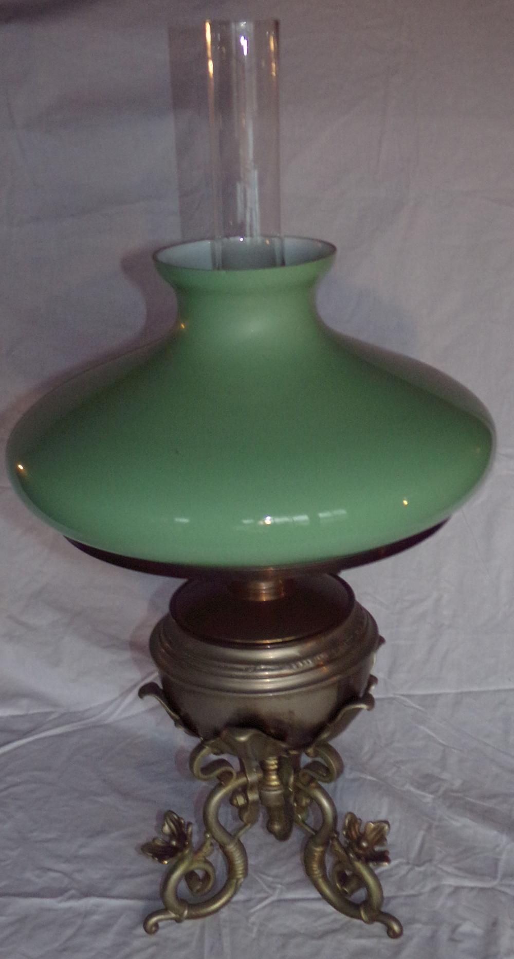 "Oil lamp having a light green cased glass shade & chimney on an ornate nickel-plated base with flower petals ending in fancy scrolled feet, font appears to be partially repaired, slight chip on top of shade, electrified, 28 ¼"" T with chimney x 8 ½ diameter"