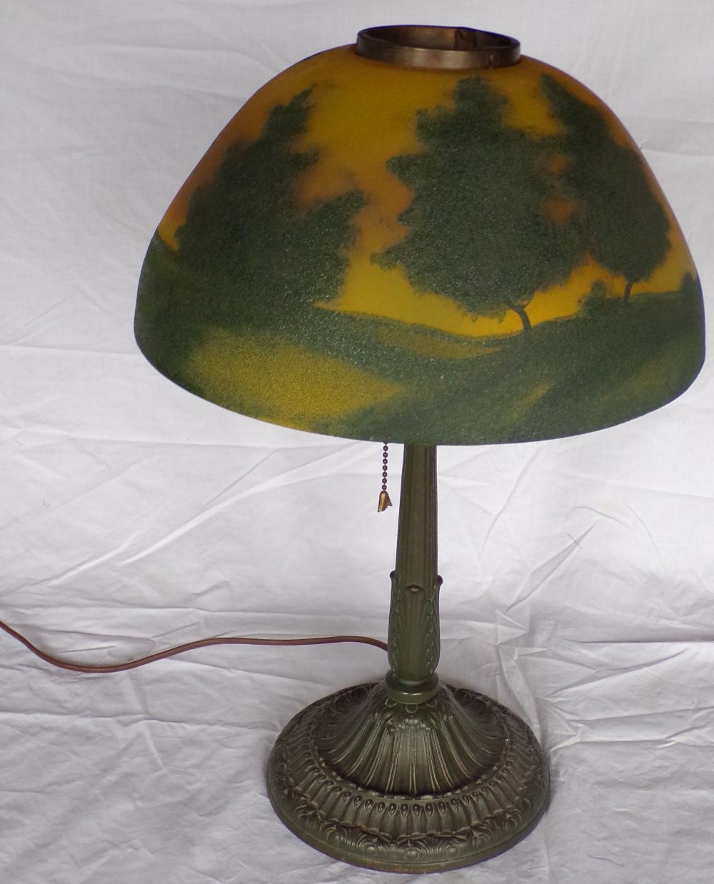 "20th century table lamp having a handpainted shade with landscape scene & trees, unsigned, mounted on a column having a leaf form design & iron weighted base, electrified, round piece which cord comes out of is not original to lamp, under side of shade has some interior chips, 18 ¼"" T x 7 1/4"" base diameter, shade 12"" diameter,"
