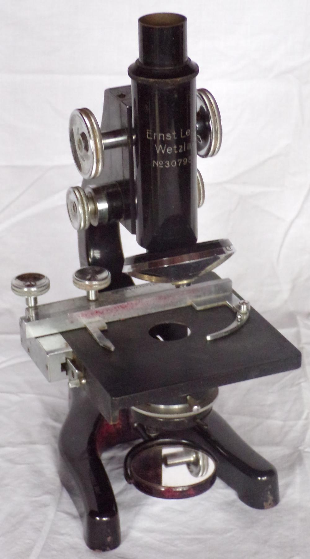"Vintage scientific microscope by Ernst Leitz Wentzler with 5 lenses & accessories, additional base mirror & black case, SN#37957, microscope 11 ¾"" T & marked at base, Thomas E Daly; case - 8 ¾"" T x 13 ½"" W x 7 1/8"" D, some paint loss & rust on feet of microscope, case shows soiling & separation of outside covering in some spots"